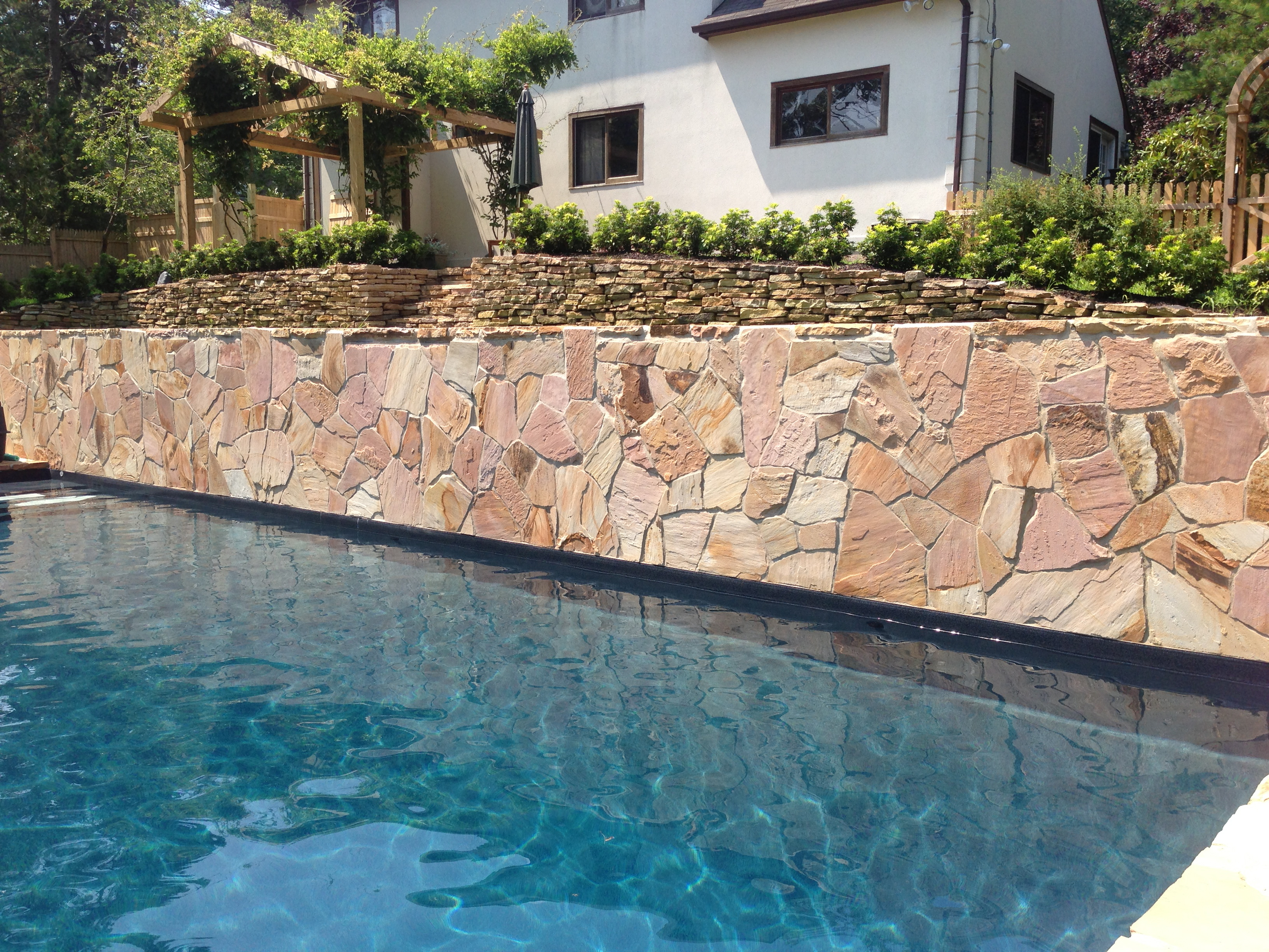 Pool with retaining wall on cliff in southampton for Pool design retaining wall